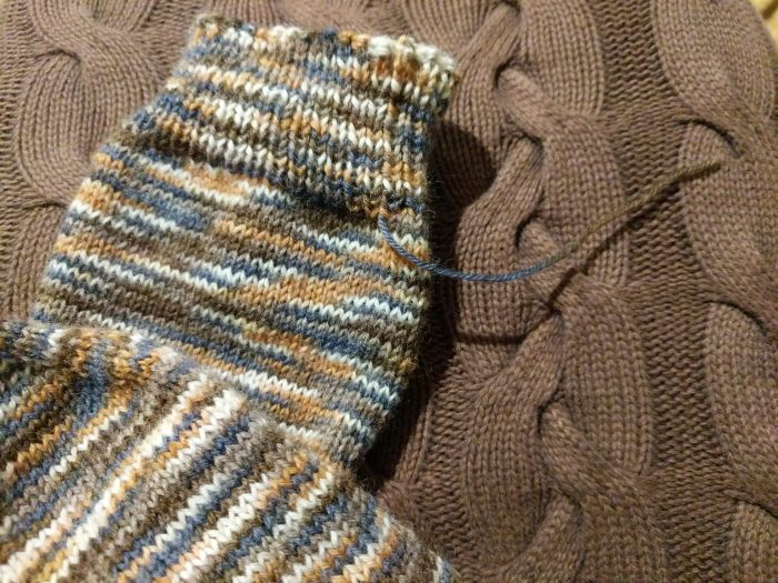 sock with loose end of yarn